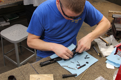 A gunsmith student applying his knowledge and skills to diagnose, troubleshoot and repair a handgun.