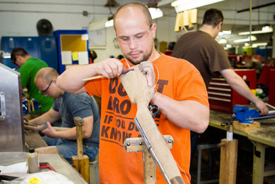 A gunsmith student preparing to install a recoil pad on his wood stock.