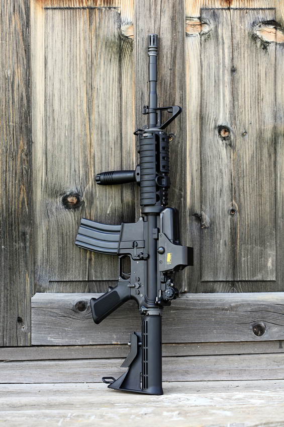 "The Black Rifle. 14,5"" AR-15 assault carbine (M4A1) with holographic sight against an old wooden door. Vertical composition."